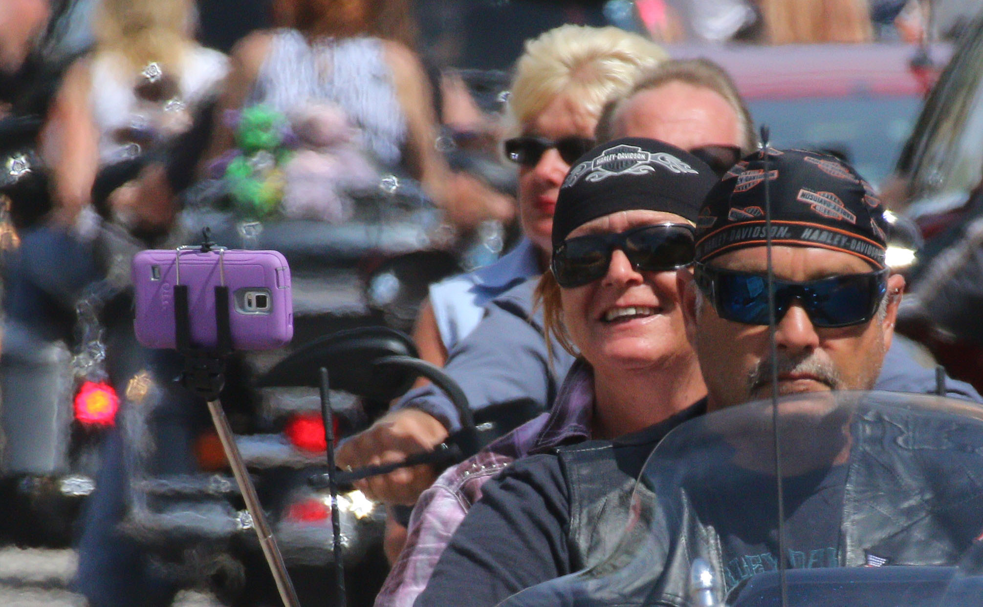 News-Journal/JIM TILLER A woman riding on the back of a motorcycle takes a selfie with her smart phone as the cruise Main Street  in Daytona Beach Friday , March 13, 2015.