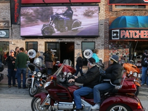 News-Journal/JIM TILLER A biker checks out a big screen TV mounted along Main Street during Bike Week 2015 in Daytona Beach.