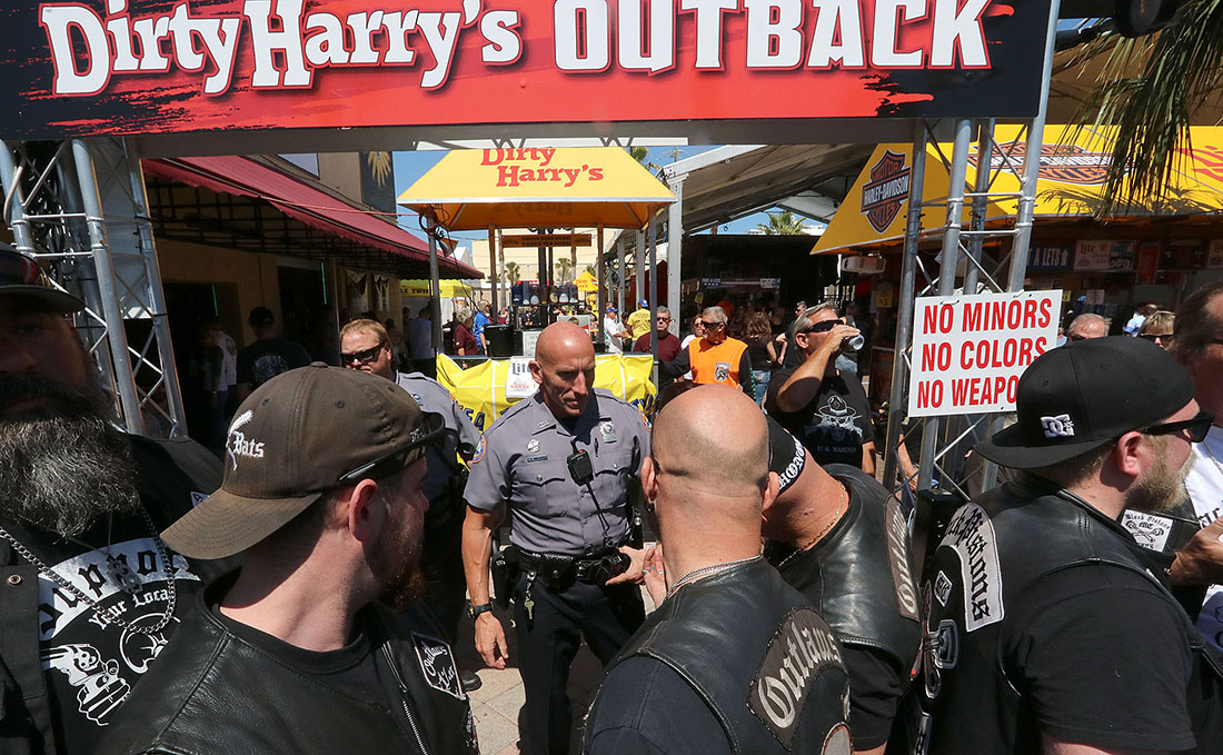 A Daytona Beach police officer talks with members of the Outlaws Motorcycle Club who were ask to leave Dirty Harry's bar on Main Street for wearing their colors as Bike Week 2017 heads into it's last weekend in Daytona Beach Saturday March 18,  2017. [News-Journal/JIM TILLER ]
