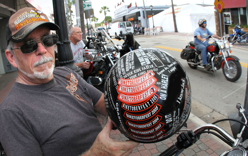 Biker Jack Huckabee shows off his helmet loaded with Biketoberfest stickers from the past 11 years along Main Street in Daytona Beach Tuesday October 11, 2011. (Photo Jim Tiller )INTERVIEWED BY HILARY