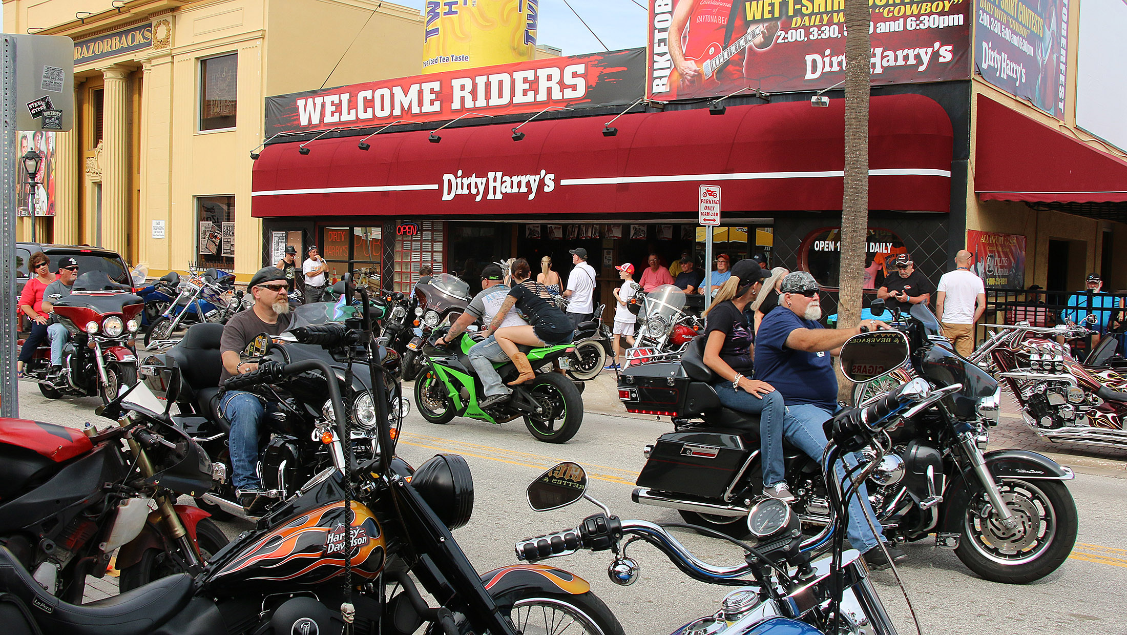Bikers ride past or stop for a drink at Dirty Harry\'s on Main Street as Biketoberfest rolls into day 2 in Daytona Beach Friday  October 16, 2015. News-Journal/JIM TILLER