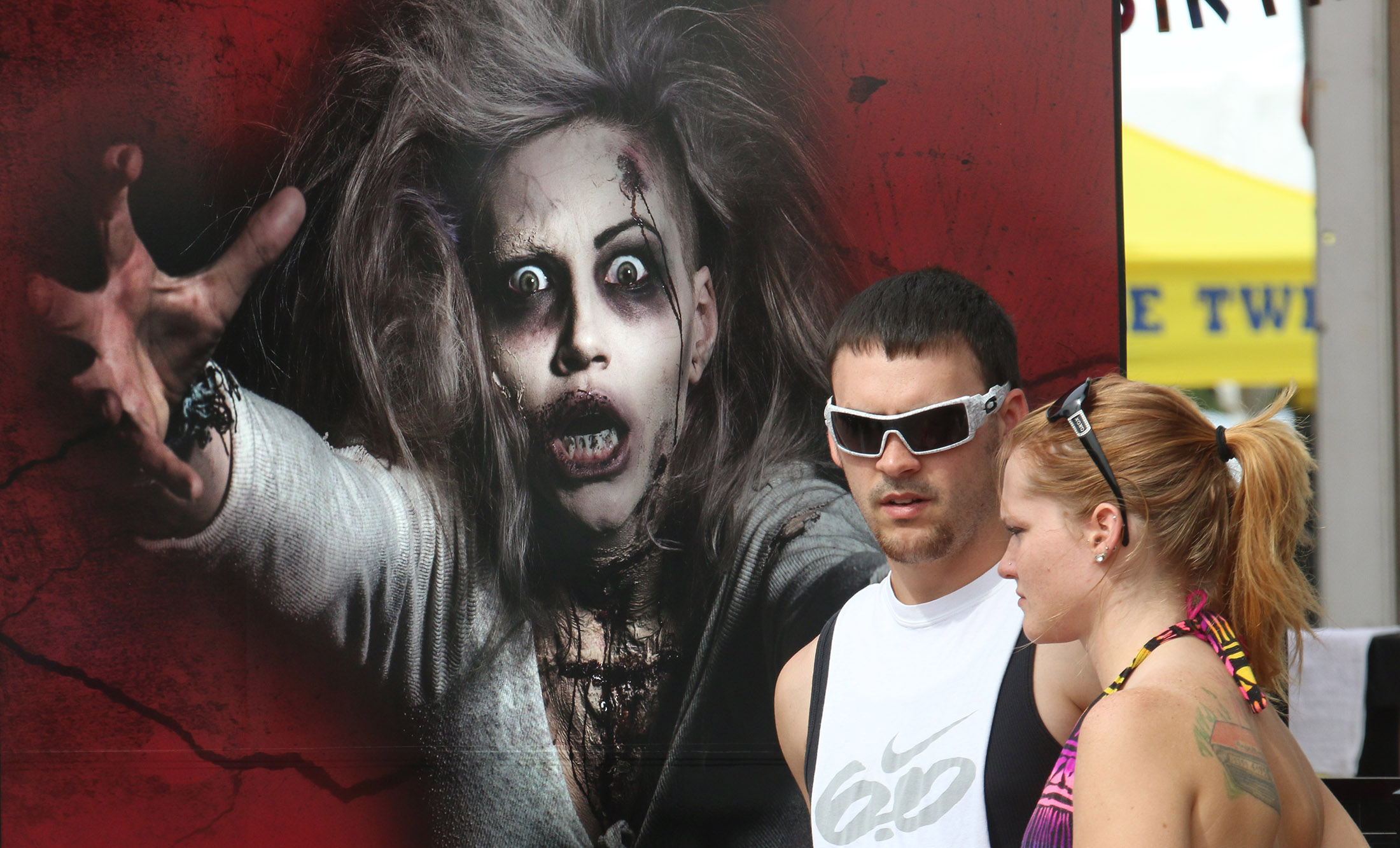 A couple walking down the sidewalk  pause next to a halloween themed advertisement along Main Street as Biketoberfest rolls into day 2 in Daytona Beach Friday  October 16, 2015. News-Journal/JIM TILLER