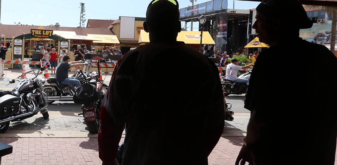 Biker watch from the shady side of Main Street as the action rolls by as Biketoberfest heads into the weekend in Daytona Beach Friday October 20, 2017. [NEWS-JOURNAL/Jim Tiller]
