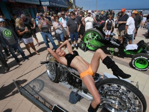 People snap photos of a model stretched out on a motorcycle at the Boardwalk Bike Show on the Boardwalk as Bike Week 2016 heads into it's final weekend in Daytona Beach Friday, March 11, 2016. News-Journal/JIM TILLER