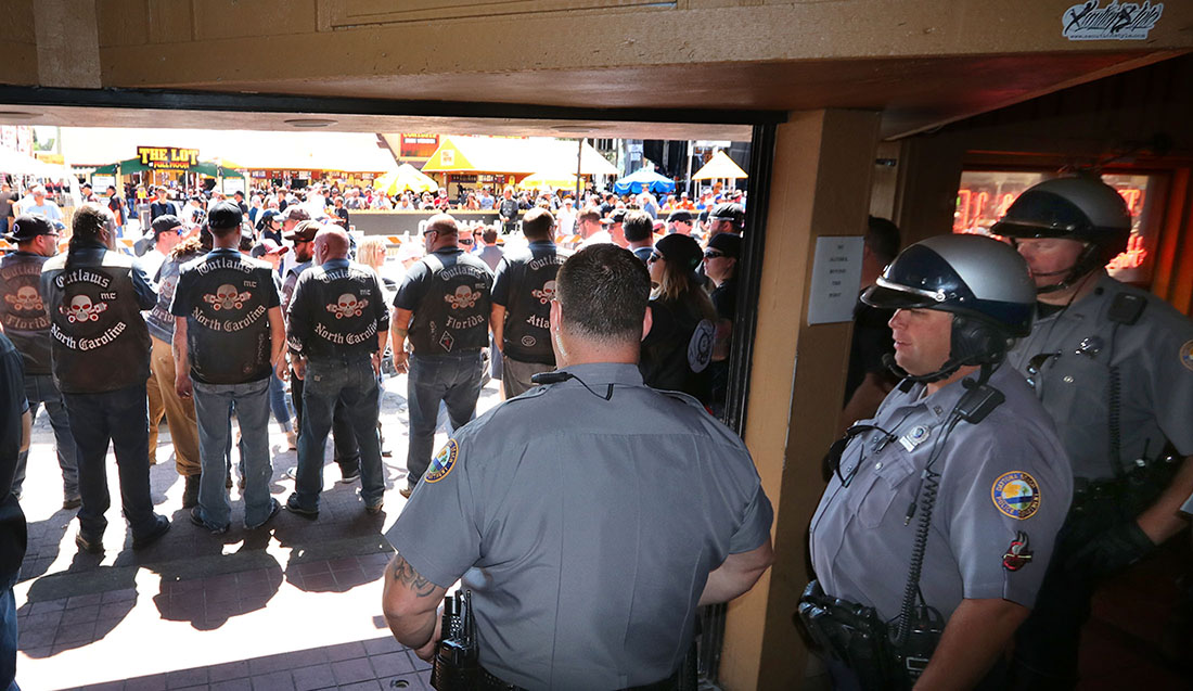 Daytona Beach Police officers keep an eye on members of the Outlaws Motorcycle Club standing shoulder to shoulder in front of Dirty Harry's bar after being ask to leave for wearing their colors inside the bar during Bike Week 2017 in Daytona Beach Saturday March 18,  2017. [News-Journal/JIM TILLER ]