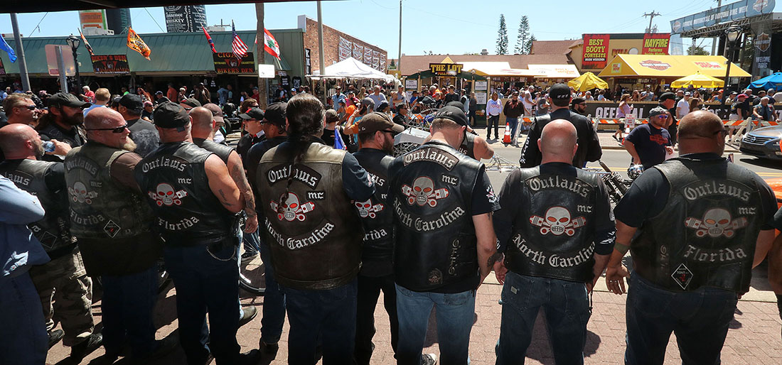 Members of the Outlaws Motorcycle Club stand shoulder to shoulder infront of Dirty Harry's bar on Main Street as Bike Week 2017 heads into it's last weekend in Daytona Beach Saturday March 18,  2017. [News-Journal/JIM TILLER ]