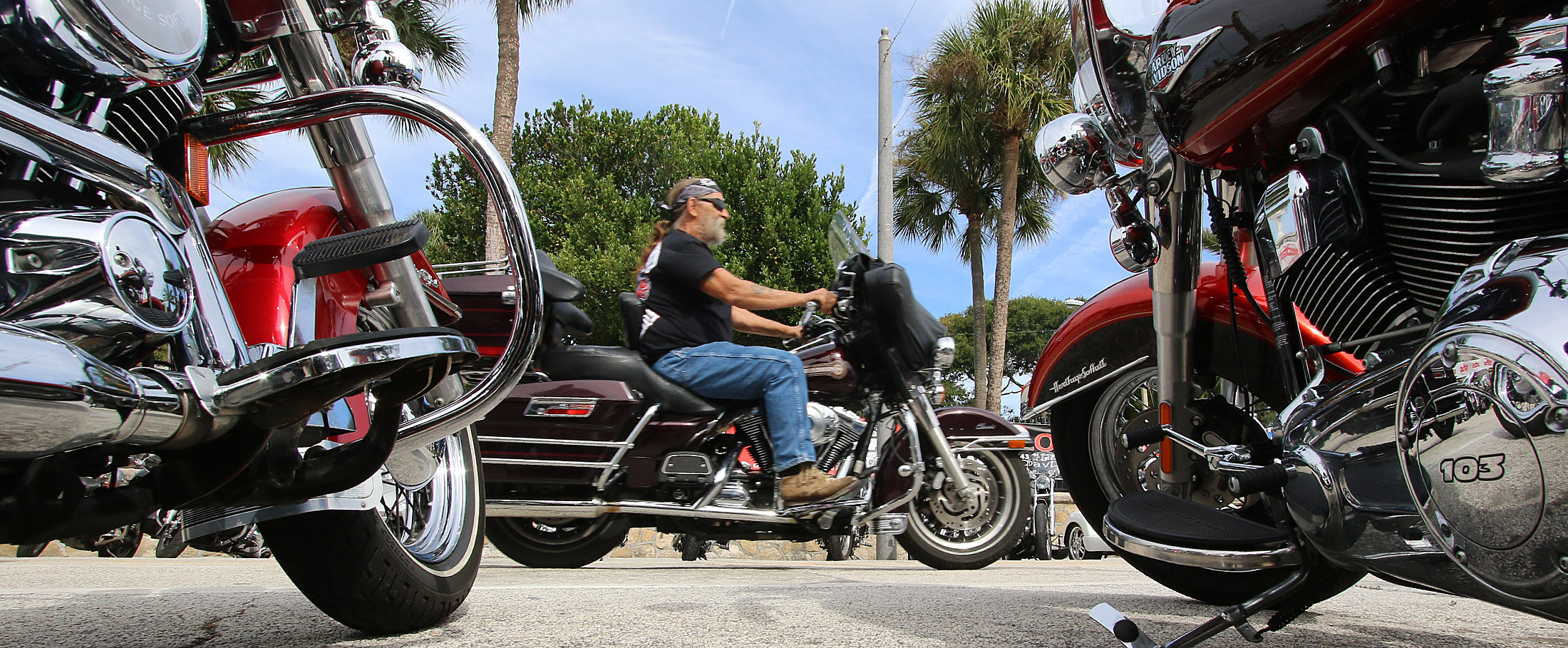 Bikers cruise past parked bike on Main Street as Biketoberfest rolls into day 2 in Daytona Beach Friday  October 16, 2015. News-Journal/JIM TILLER