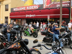 Bikers ride past or stop for a drink at Dirty Harry's on Main Street as Biketoberfest rolls into day 2 in Daytona Beach Friday  October 16, 2015. News-Journal/JIM TILLER