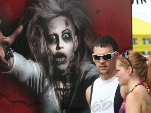 A couple walking down the sidewalk  pause next to a halloween themed advertisement along Main Street as Biketoberfest rolls into day 2 in Daytona Beach Friday  October 16, 2015. News-Journal/JIM TILLER